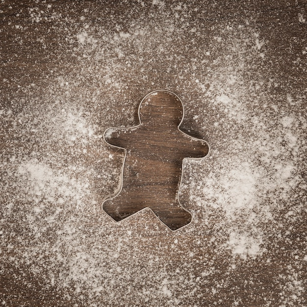 Top view gingerbread man cookie cutter with flour Free Photo