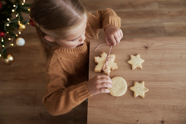 Vista dall'alto della ragazza che imballa i biscotti per babbo natale Foto Gratuite