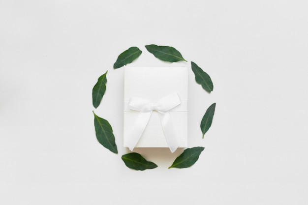 Top view of gist box in round circle frame of green leaves. wedding flat lay Premium Photo