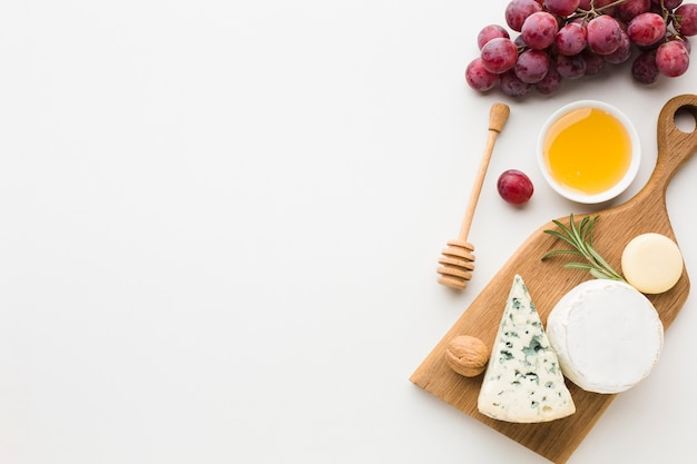 Top view gourmet assortment of cheese on wooden cutting board with copy space Free Photo