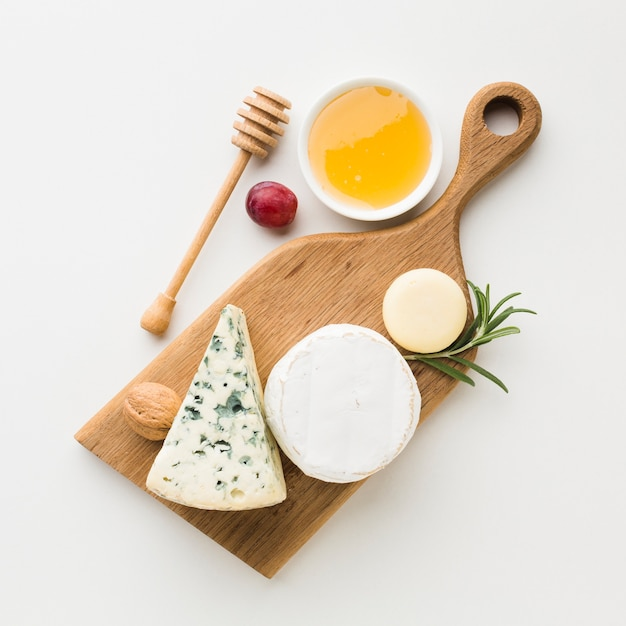 Top view gourmet assortment of cheese on wooden cutting board Free Photo