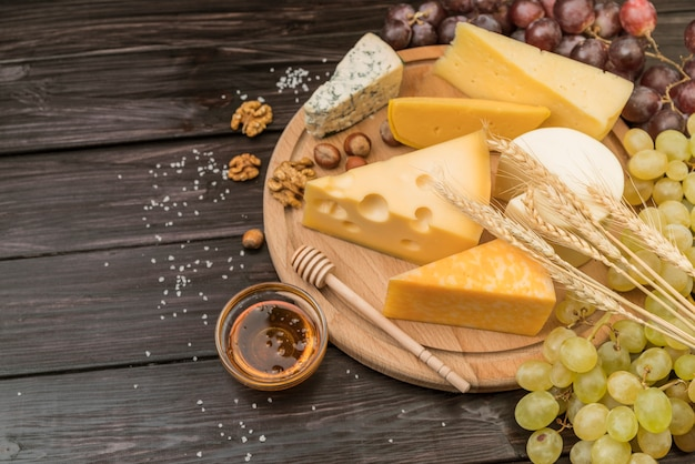 Top view gourmet cheese with honey and grapes Free Photo