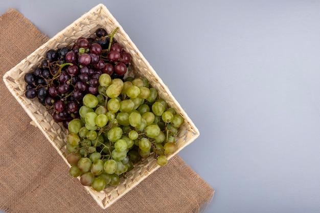 Vista dall'alto di uva nel cesto su tela di sacco su sfondo grigio con copia spazio Foto Gratuite