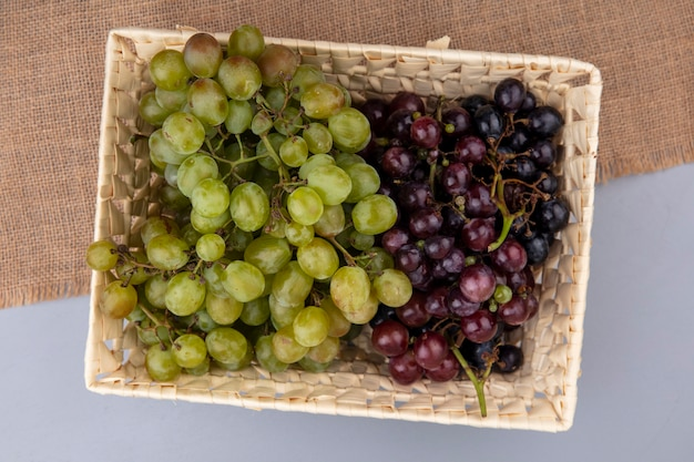 Vista dall'alto di uva nel cesto su tela di sacco su sfondo grigio Foto Gratuite