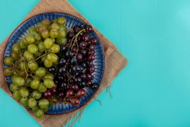 Vista dall'alto di uva nella piastra su tela di sacco su sfondo blu con copia spazio Foto Gratuite