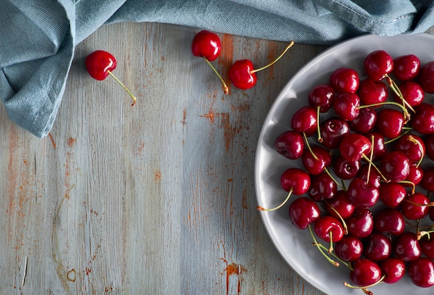 Top view on the gray plate of cherries on rustic wooden with text space Premium Photo