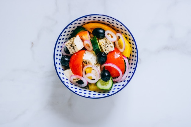 Top view greek salad with olive oil on marble. Premium Photo