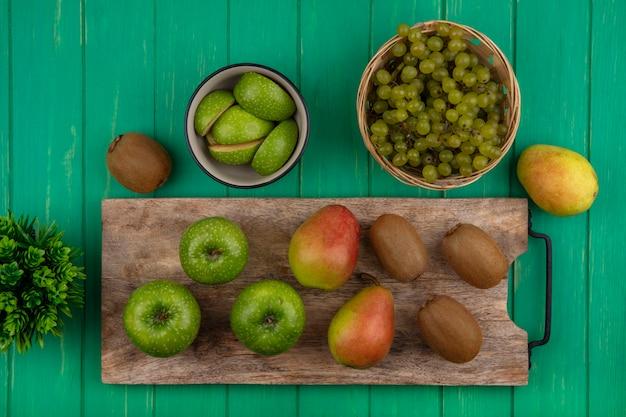 Вид сверху зеленые яблоки с киви и грушей на разделочной доске и зеленый виноград в корзине на зеленом фоне Бесплатные Фотографии