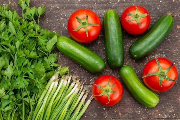 Cetrioli verdi di vista superiore freschi e maturi con i pomodori rossi e verdi sull'alimento marrone dell'albero della pianta vegetale Foto Gratuite