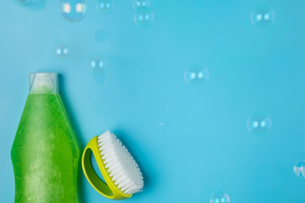 Top view green detergent and brush arrangement Free Photo
