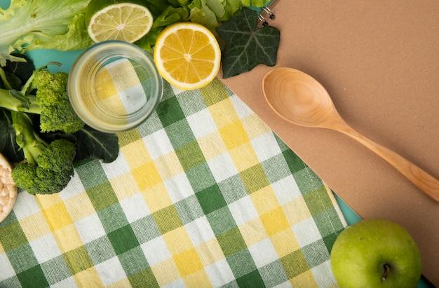トップビューの緑の果物と野菜のブロッコリーレタスアイビーリーフガラスの水木のスプーンアップルスライスレモンとライムのテーブルクロスにコピースペース 無料写真