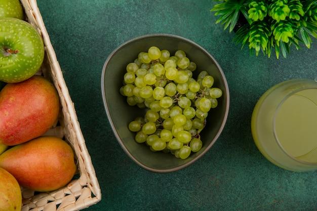 緑の背景にジュースと青リンゴとバスケットの梨とボウルに緑のブドウの上面図 無料写真