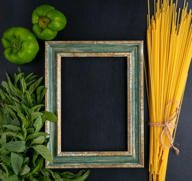 Top view of greenish-gold frame with raw spaghetti mint and bell pepper on a black surface Free Photo