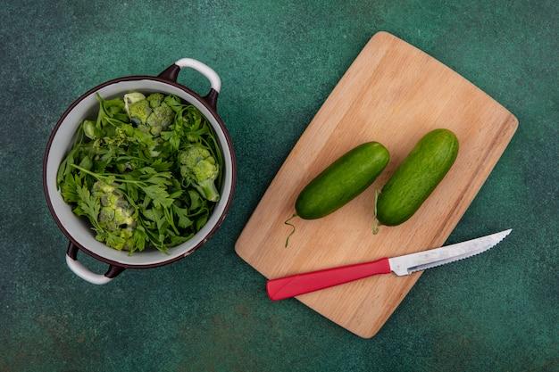 緑の背景にナイフでまな板にきゅうりと鍋のトップビュー緑 無料写真