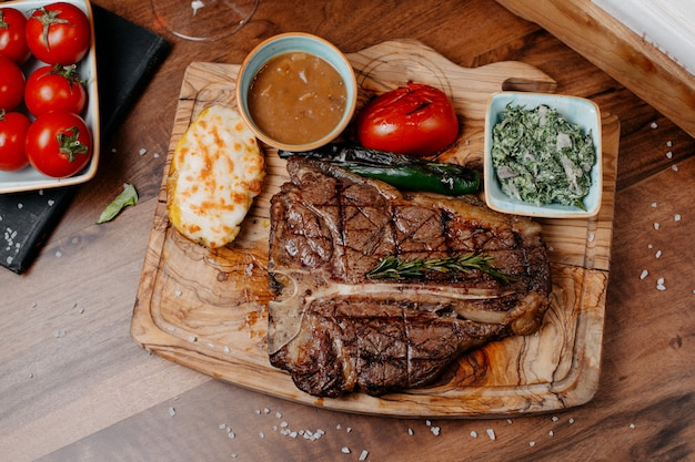 Top view of griled beef steak served with vegetables and sauce on a wooden board Free Photo