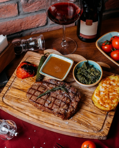 Top view of grilled beef steak with naked potato and sauce on a wooden board Free Photo