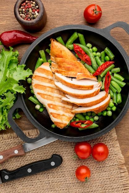 Вид сверху жареной курицы и гороха на сковороде с перцем чили и помидорами Бесплатные Фотографии