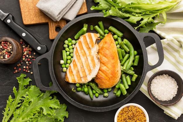 Вид сверху жареный цыпленок и горох в сковороде с приправами Бесплатные Фотографии