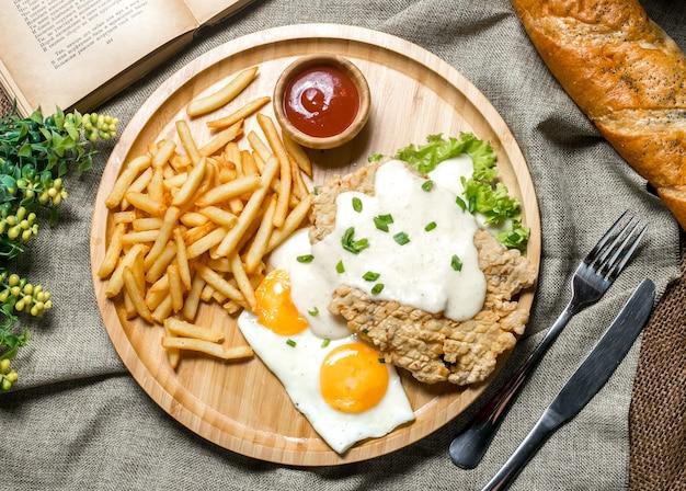상위 뷰 구운 닭고기 필렛 소스에 튀긴 계란 케첩 봄 양파 양상추와 감자 튀김 보드 무료 사진