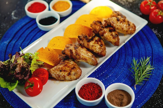 Top view of grilled chicken wings served with fried potatoes and fresh salad Free Photo