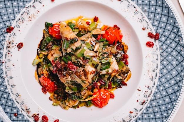접시에 튀긴 양파 토마토 피망과 채소와 상위 뷰 구운 치킨 무료 사진