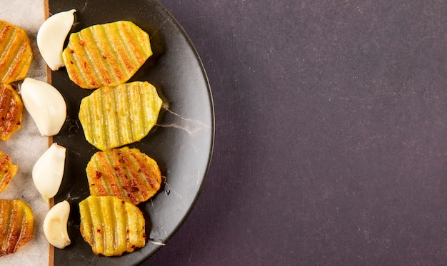 어두운 회색 배경에 복사 공간 왼쪽에 상위 뷰 구운 감자와 마늘 무료 사진