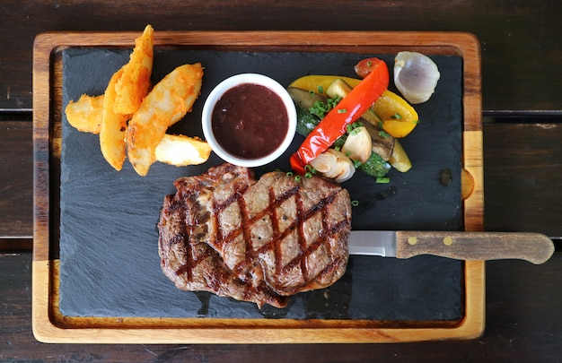 Top view of grilled ribeye steak with red wine sauce served on hot stone plate Premium Photo