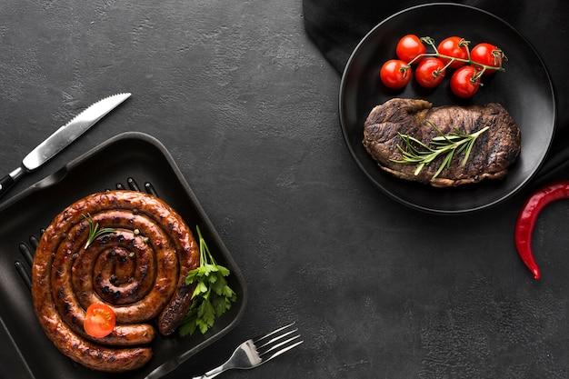 Вид сверху жареная колбаса и вкусный стейк готовые к употреблению Premium Фотографии