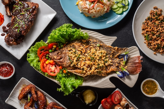 Top view of group of food on wooden, deep fried fish in the middle, top view. Premium Photo