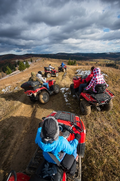 Top view of a group of people riding an atv on a mountain road under a sky with clouds in sunny autumn day Premium Photo