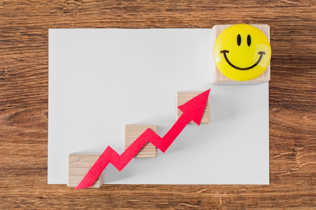 Vista dall'alto della freccia di crescita e della faccina sorridente Foto Gratuite