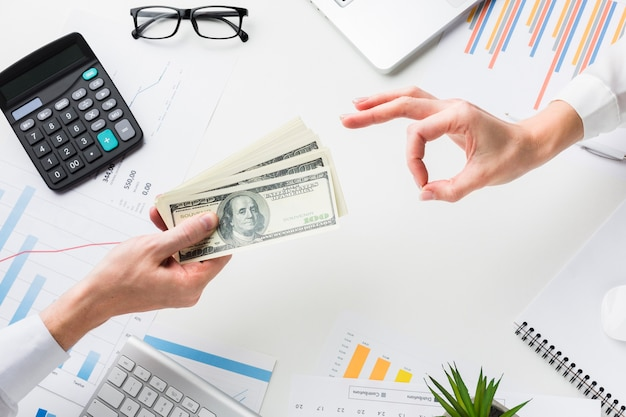 Top view of hand accepting money over desk Free Photo