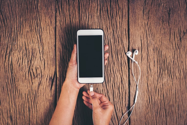 Top view hand charging phone on wood background Free Photo