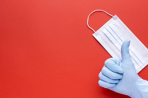 Vista dall'alto della mano che dà i pollici in su con maschera medica e copia spazio Foto Gratuite