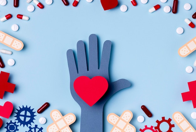 Top view hand holding heart surrounded by pills Free Photo