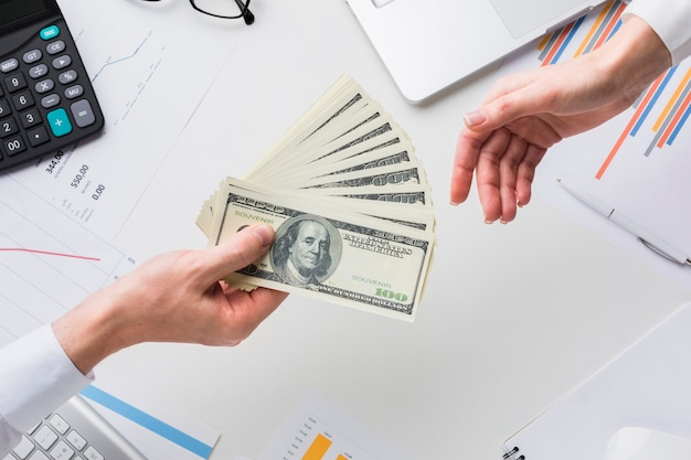 Top view of hand holding money over desk Free Photo