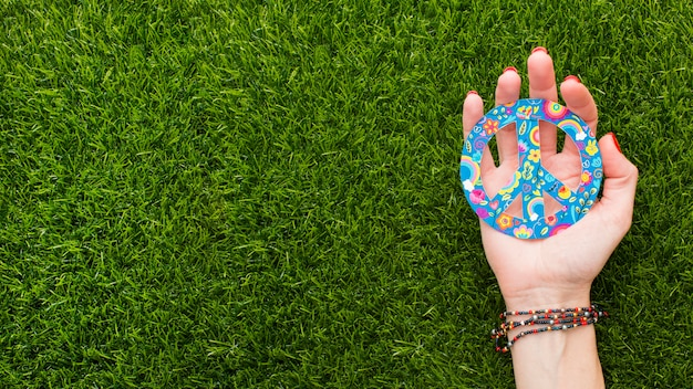 Top view of hand holding peace sign on grass with copy space Free Photo
