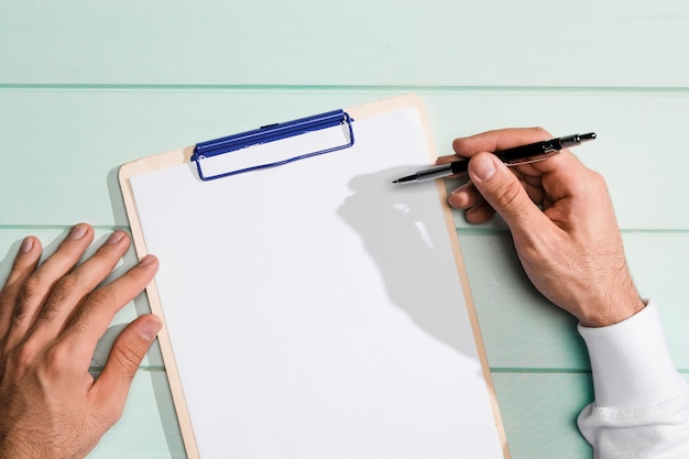 Top view hand holding a pen above copy space clipboard Free Photo