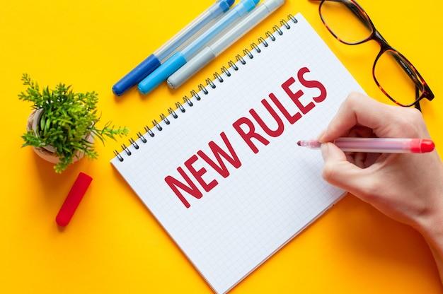 상위 뷰, 노란색 테이블에 노트북, 펜, 안경, 계산기 및 녹색 꽃과 함께 새로운 규칙 목록을 작성하는 연필을 들고 손. 비즈니스 및 교육 개념 프리미엄 사진