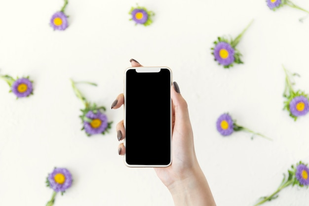 Top view hand holding a phone surrounded by flowers Free Photo