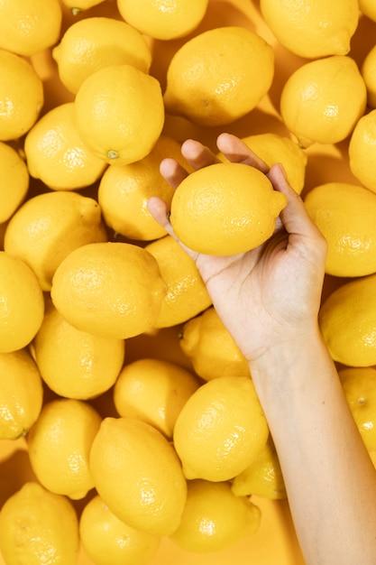 Top view hand holding raw lemonade Free Photo