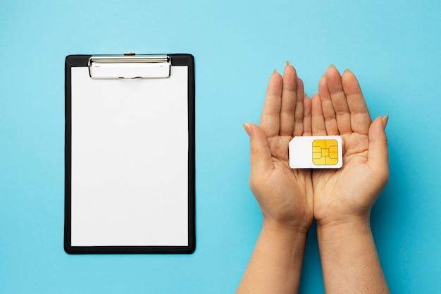 Vista dall'alto della mano che tiene la scheda sim con appunti Foto Gratuite