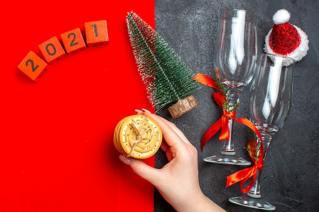 Top view of hand holding stacked cookies christmas tree numbers santa claus hat on red and black background Free Photo