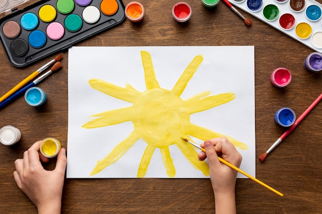 Top view of hand painting a sun Free Photo