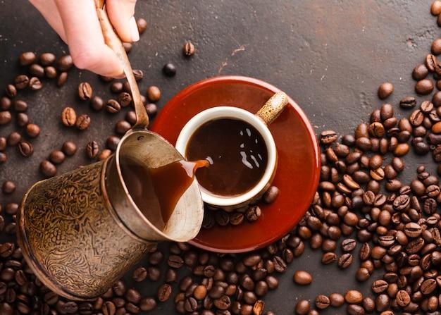 Вид сверху рука наливает кофе в чашку Бесплатные Фотографии