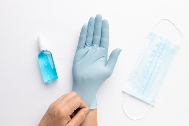 Vista dall'alto della mano che indossa il guanto con disinfettante per le mani e maschera medica Foto Gratuite