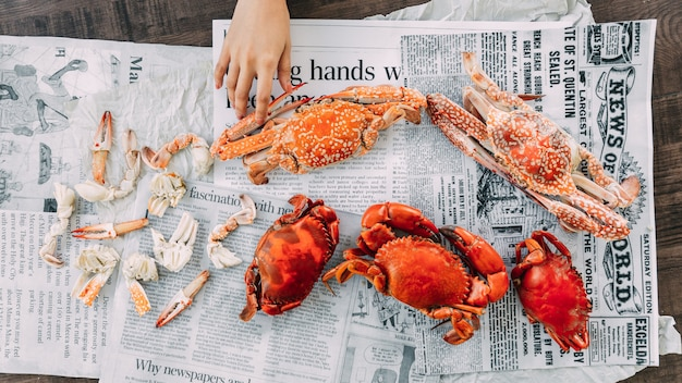 Top view of hand touching steamed flower crabs and giant mud crabs with separated parts of steamed crab Premium Photo