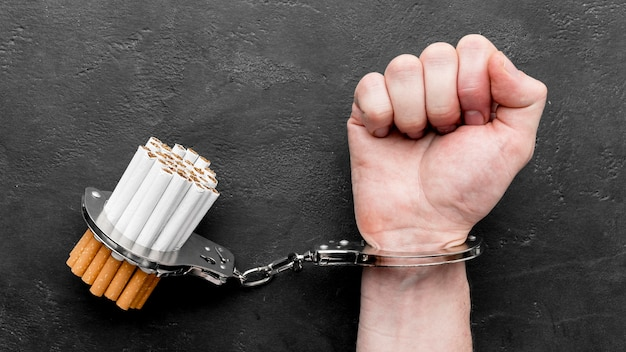 Top view hand with handcuffed cigarettes Free Photo