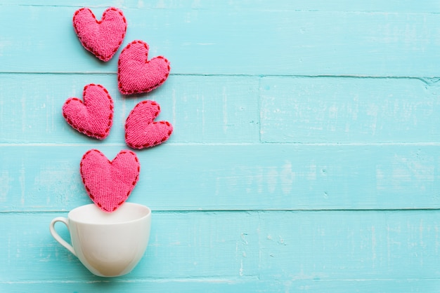 Top view  of handmade pink heart on blue and white color wooden background Premium Photo