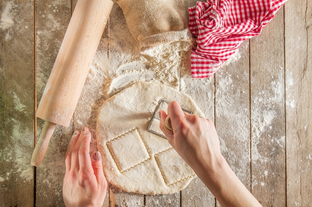 Top view of hands cutting the dough Free Photo